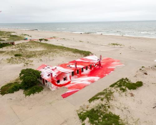 German artist Katharina Grosse spray-paints a building at Fort Tilden, NY